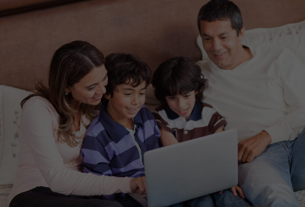 Happy family with a laptop computer in bed.jpeg